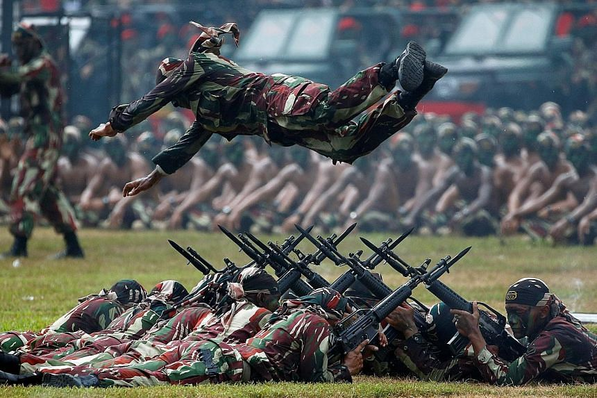 A Special Forces soldier performing a leap over a row of rifles topped with bayonets during celebrations for the 67th anniversary of the Indonesian Army's Special Forces in Jakarta yesterday. The troops conduct special operations missions such as unc
