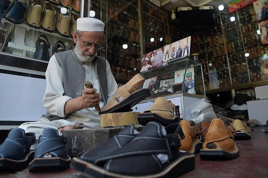 (Left) A Pakistani shoemaker in Peshawar making a pair of traditional chappal, which has inspired French shoe designer Christian Louboutin's new sandals (above).