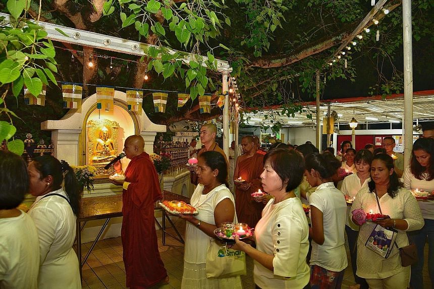 Venerable K. Gunaratana (with microphone) leading a procession around the bodhi tree compound at the Sri Lankaramaya Buddhist Temple, with attendees carrying plates of flowers and candles.