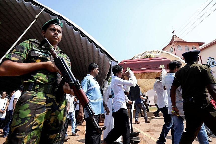 A soldier on the alert at yesterday's funeral in Negombo of an eight-month-old victim of the Easter Sunday blasts.