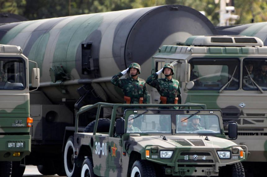 People's Liberation Army soldiers salute in front of nuclear-capable missiles during a parade. China has focused research and development on hypersonic missiles that can carry nuclear payloads.
