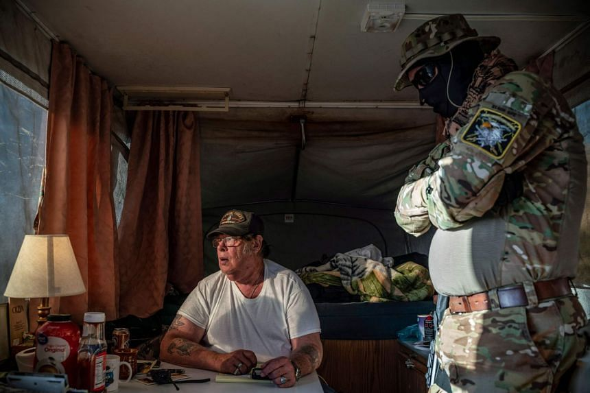 Striker (left), the leader of the Constitutional Patriots New Mexico Border Ops Team militia, speaks with Viper (right) inside the team's camper van near the US-Mexico border.