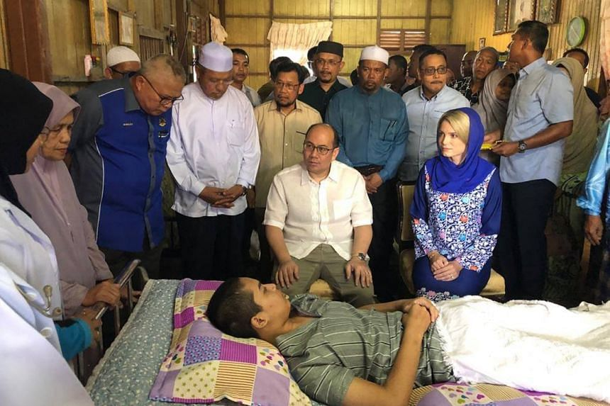 The Crown Prince of Kelantan, Tengku Muhammad Faiz Petra, and his wife Sofie Louise Johansson (both seated) visiting brain cancer patient Hakim Danial, 17, at his home on Tuesday.