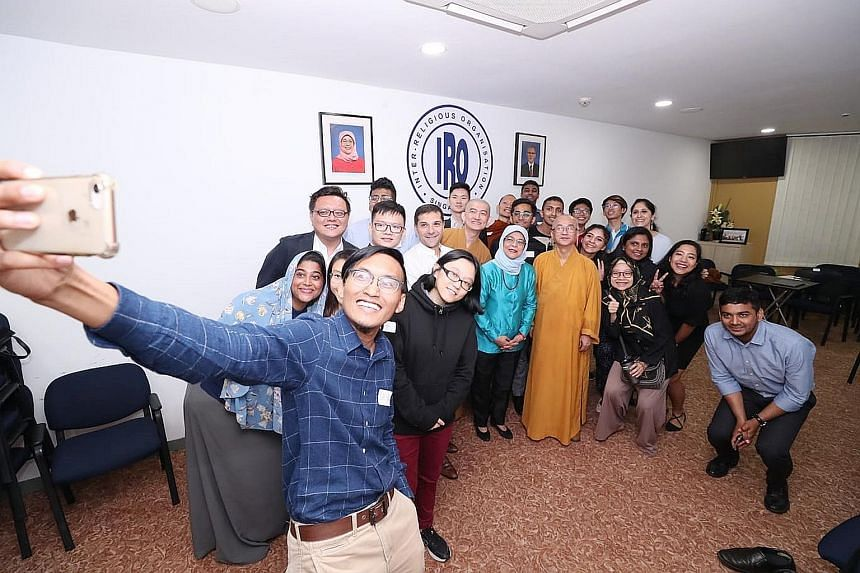 Inter-Religious Organisation youth leader Mohamad Saiful Md Anuar taking a wefie with President Halimah Yacob, who was flanked by IRO president Ben J. Benjamin and Venerable Kwang Phing, the IRO's vice-president, as well as other participants yesterd