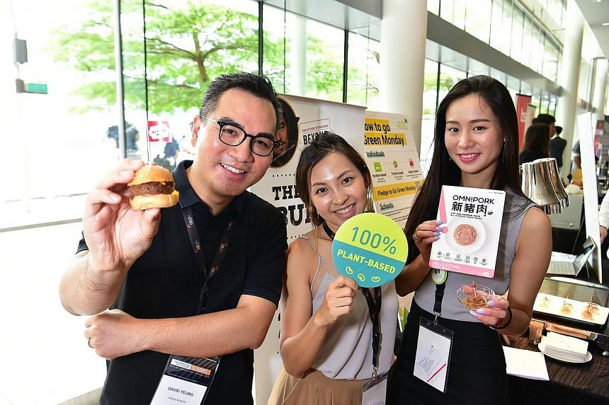 Mr David Yeung, founder and chief executive of social venture group Green Monday, holding a burger made from 100 per cent plant-based meat products at the Food Industry Asia Food for the Future Summit at Marina Bay Sands yesterday. With him are his s