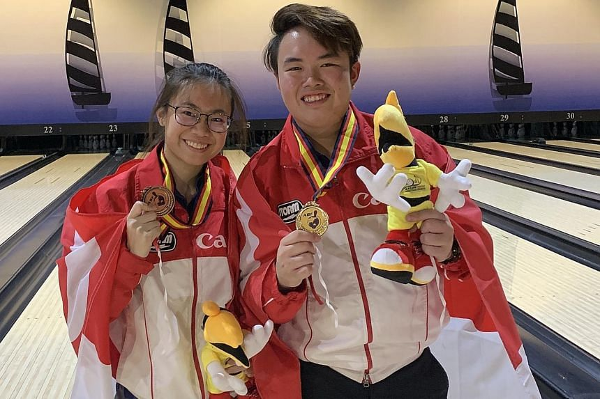 Singapore bowlers Charlene Lim and Xavier Teo posing with their medals at the Asian Youth Tenpin Bowling Championships yesterday. Lim won bronze in the Masters final while Xavier clinched gold. PHOTO: SINGAPORE BOWLING FEDERATION