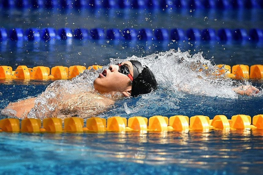Bradley Tan of ACS (I) pushing hard yesterday during the backstroke leg of his A Division 200m individual medley final. He won the event in a meet record of 2min 10.27sec, bettering the previous mark of 2:10.49. ST PHOTO: CHONG JUN LIANG
