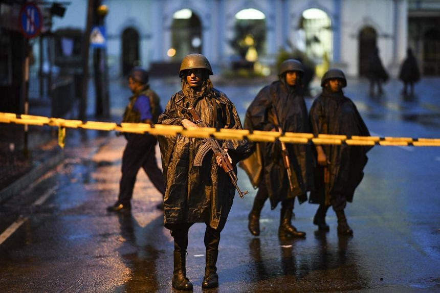 Sri Lankan soldiers standing guard under the rain at St Anthony's Shrine in Colombo on April 25, 2019. Abdul Lathief Jameel Mohamed came to the attention of the authorities in 2014 when he was linked to several counter-terrorism targets.