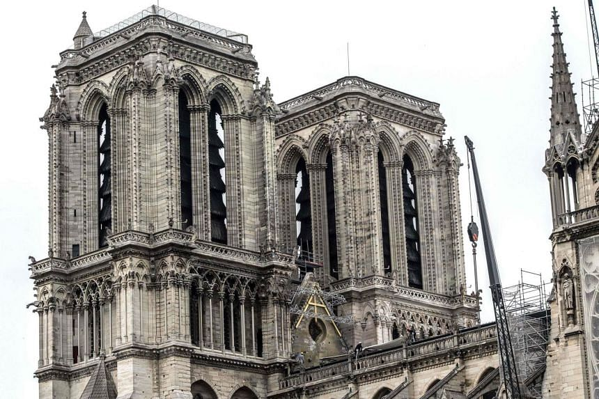 Workers install protective tarps on the roof of Notre-Dame Cathedral in Paris, on April 23, 2019.