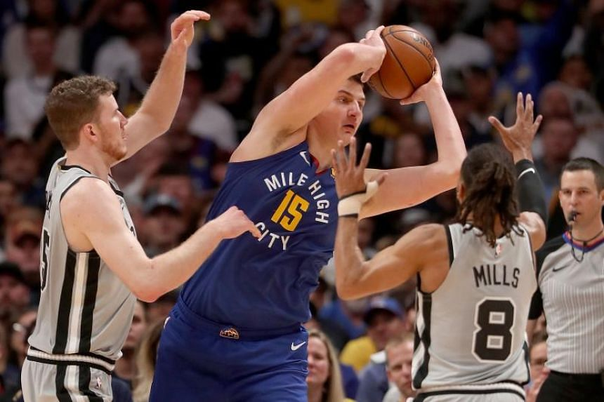 Denver Nuggets' Nikola Jokicis (centre) is guarded by Jakob Poeltl (#25) and Patty Mills (#8) of the San Antonio Spurs in the third quarter during Game Five of the first round of the 2019 NBA Western Conference Playoffs at the Pepsi Center on April 2