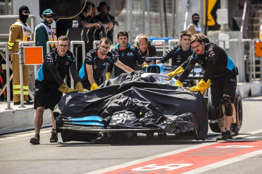 Mechanics push the car of British Formula One driver George Russell of Williams back to their team's garage after an accident during the first practice session for the 2019 Formula One Grand Prix of Azerbaijan at the Baku City Circuit in Baku, Azerba