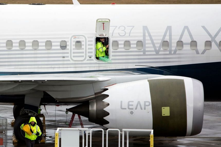 Workers are pictured next to a Boeing 737 Max 9 plane on the tarmac at Boeing in Renton, Washington.