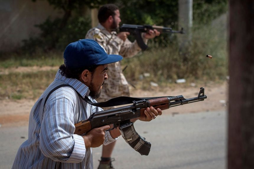 Fighters loyal to the internationally recognised Government of National Accord fire their weapons during clashes with forces loyal to strongman Khalifa Haftar.