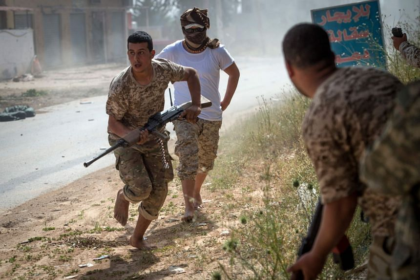 Fighters loyal to the internationally recognised Government of National Accord run for cover during clashes with forces loyal to strongman Khalifa Haftar.
