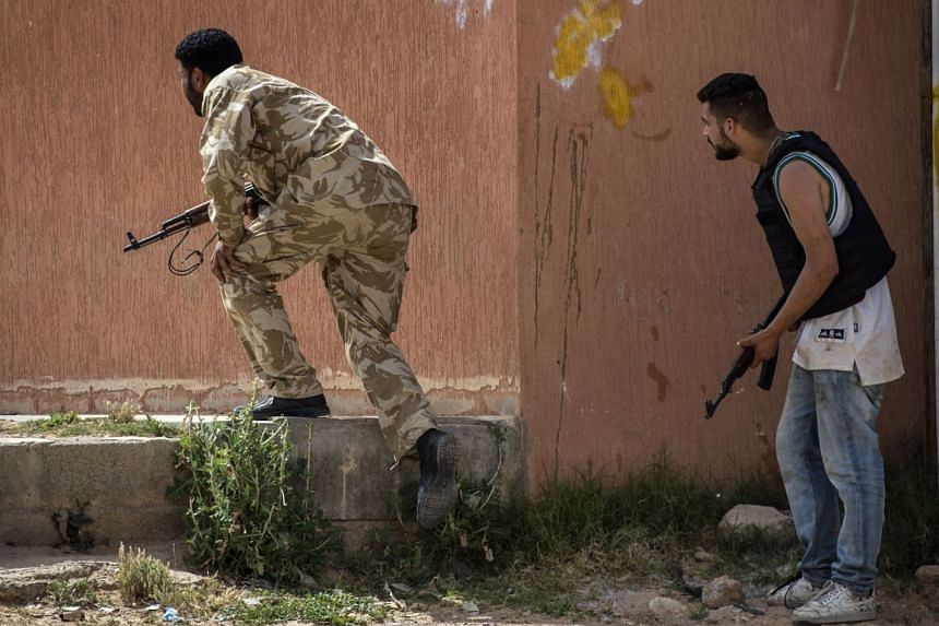 Fighters loyal to the internationally recognised Government of National Accord hold a position during clashes with forces loyal to strongman Khalifa Haftar.