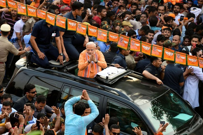 Indian PM and leader of the Bharatiya Janata Party (BJP) Narendra Modi (centre) gestures to supporters during a roadshow in Varanasi, on April 25, 2019.