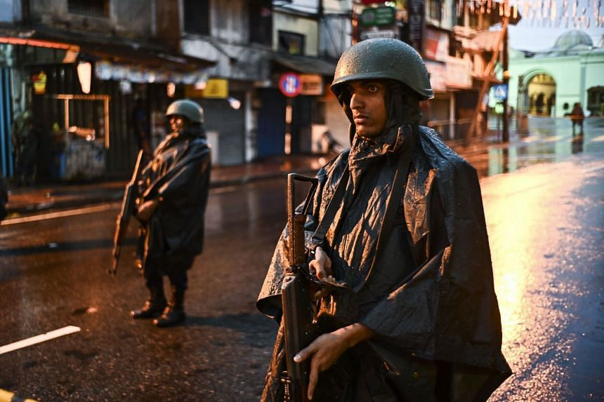 Sri Lankan soldiers stand guard under the rain at St. Anthony's Shrine in Colombo.