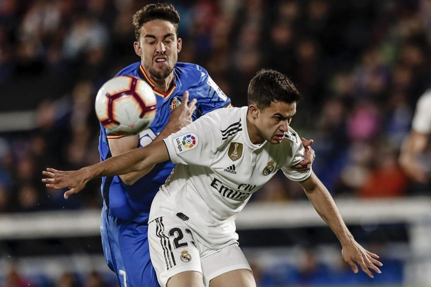 Getafe's Jaime Mata (left) vies for the ball with Real Madrid's Sergio Reguilon.