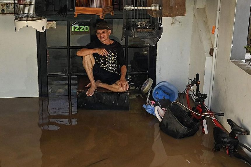 A man sitting outside his house in a flooded area of Jakarta yesterday. Torrential rain triggered flooding in parts of the Indonesian capital on Thursday night, the country's disaster agency said yesterday, forcing the evacuation of residents. Heavy