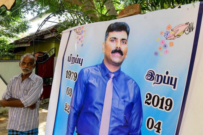 Mr Velusami Raju beside a banner of his son Ramesh Raju, who died stopping a suicide bomber in the Zion evangelical church in Batticaloa, Sri Lanka.