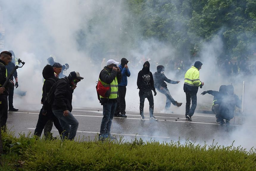 Smoke billows as demonstrators clash with riot police in Strasbourg.
