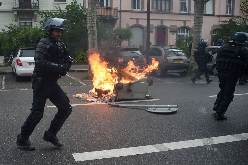 Riot police run past a burning rubbish container in Strasbourg.