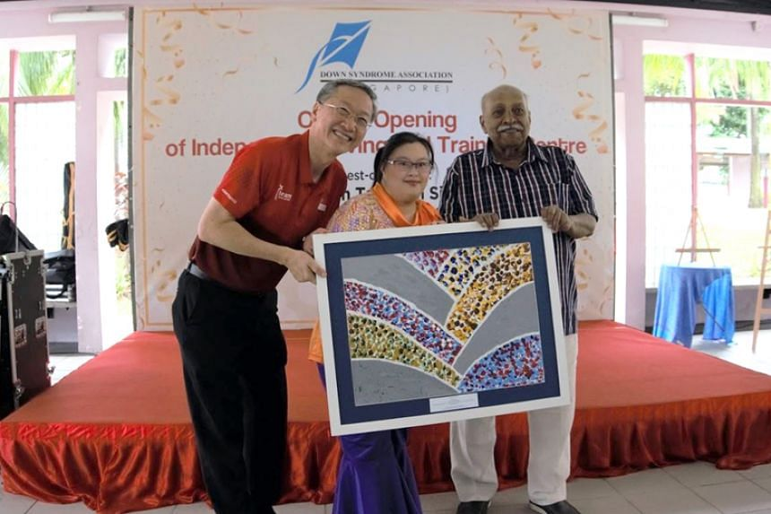 Down Syndrome Association (Singapore) chairman R Sivanandam and Down Syndrome Association (Singapore) member Chen Wanyi present a token of appreciation to Minister of State for Foreign Affairs and Social and Family Development Sam Tan during the open