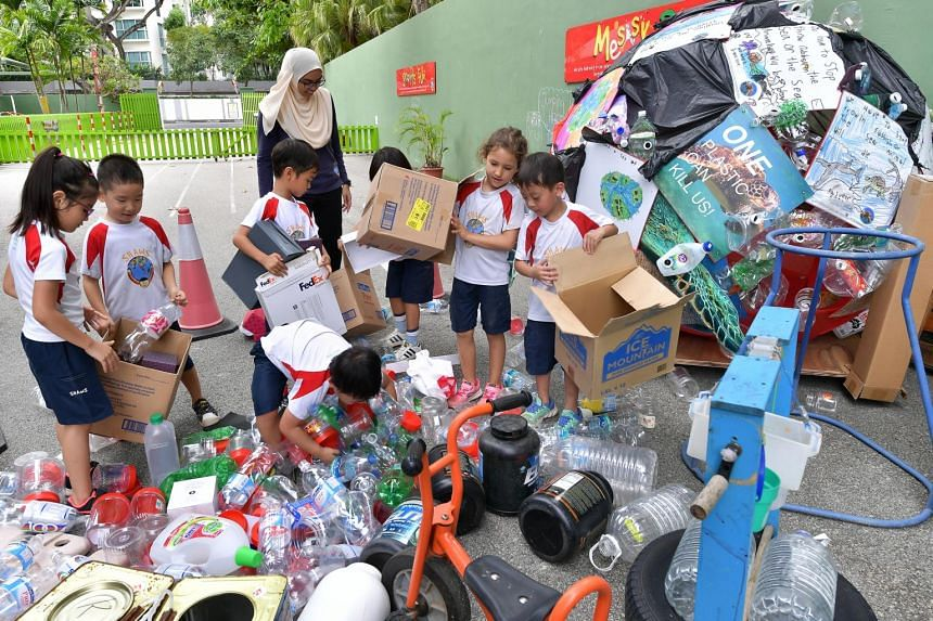 Children from Shaws Preschool group sifting through used or donated items, such as plastic bottles, tattered books, cartons and even a laminating machine worn down from use in the school office.