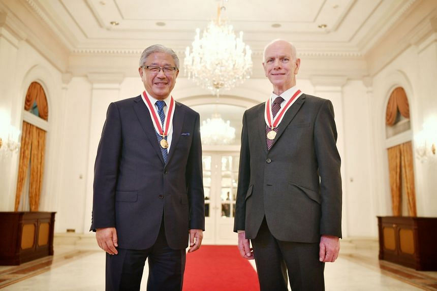 Professor Victor J. Dzau (left) and Professor John O'Reilly received their award from President Halimah Yacob at the Istana.