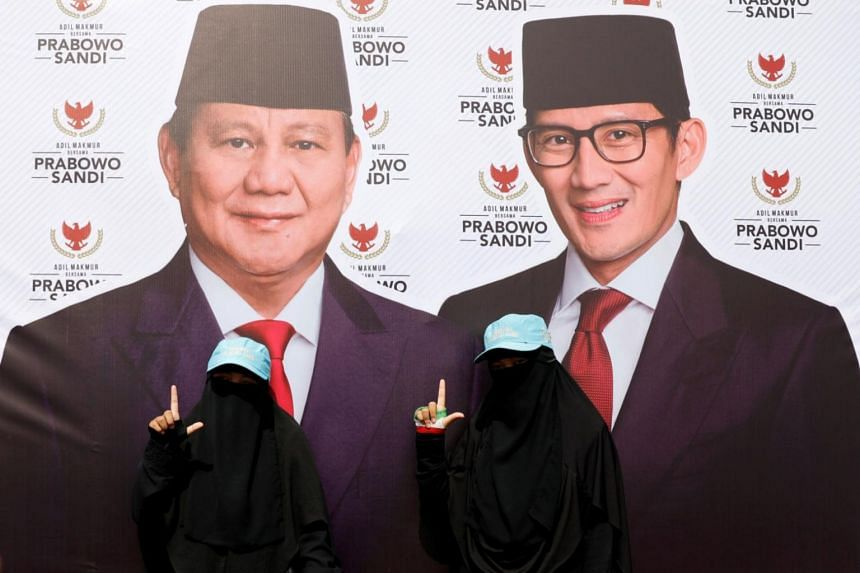 Women wearing full-face veil gesture next to a banner of presidential candidates Prabowo Subianto, and his running mate Sandiaga Uno, as they attend a campaign rally in Bandung, West Java province, Indonesia, on March 28, 2019.