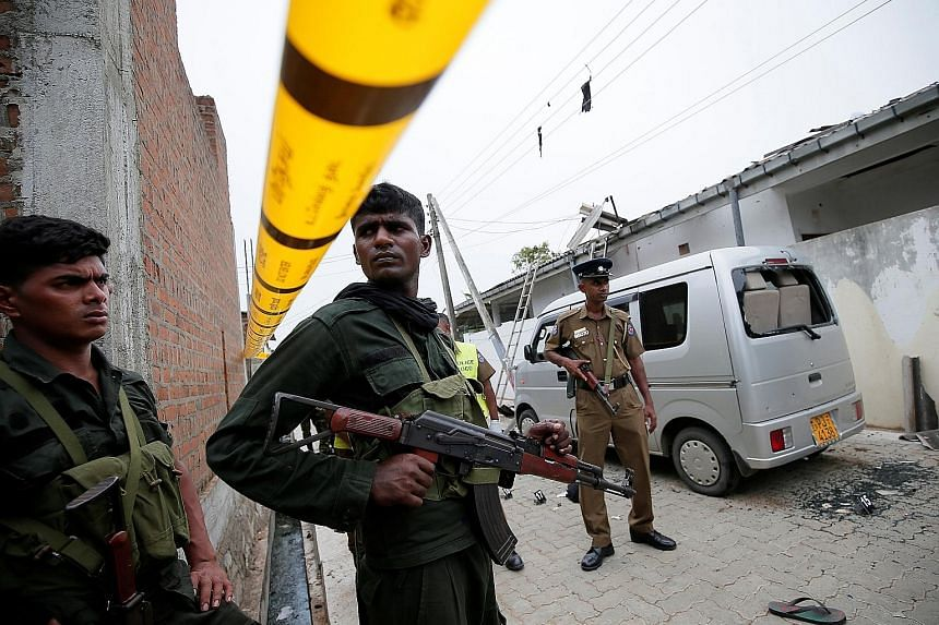 Sri Lankan security personnel at the site of an overnight gun battle between troops and suspected Islamist militants on the east coast of Sri Lanka yesterday. The operation in Sainthamaruthu in Ampara district followed a tip-off that people linked to