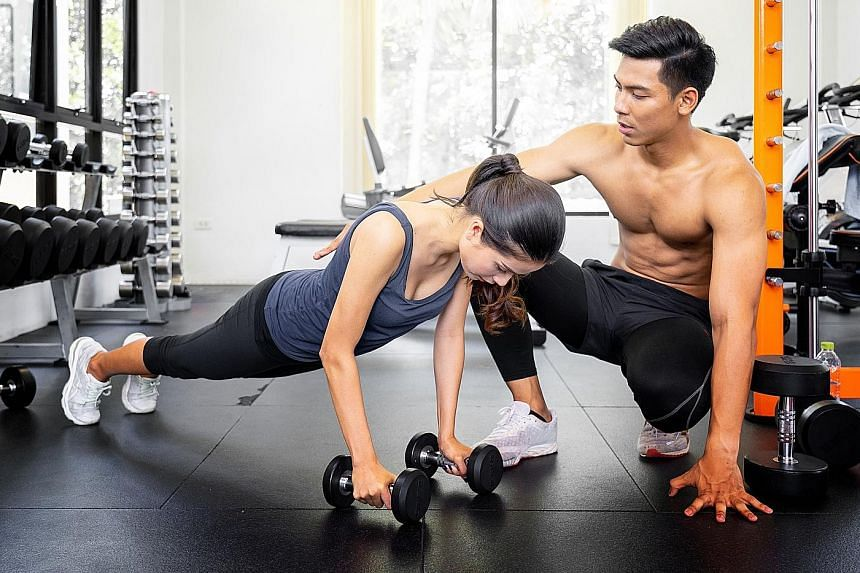 A personal trainer showing his trainee the high plank start position for bicep curls. PHOTO: ISTOCKPHOTO