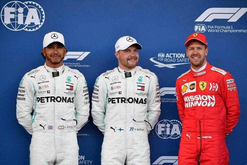 Pole position winner Mercedes' Finnish driver Valtteri Bottas (centre) poses with second placed Mercedes' British driver Lewis Hamilton (left) and third placed Ferrari's German driver Sebastian Vettel after the qualifying session for the the Formula