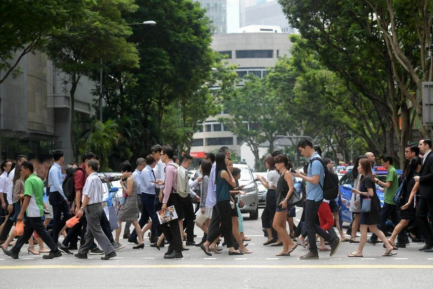 Pedestrians crossing a road in Singapore's central business district during the lunch hour.