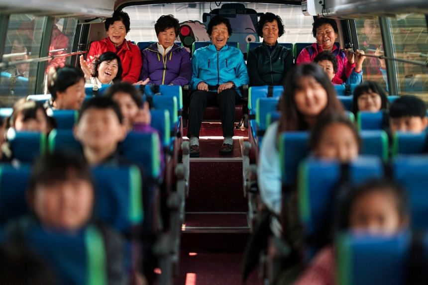 Grandmothers in the bus on a school trip in South Korea. The school decided to enrol older villagers after no child could be found to enrol as a first grader this year.