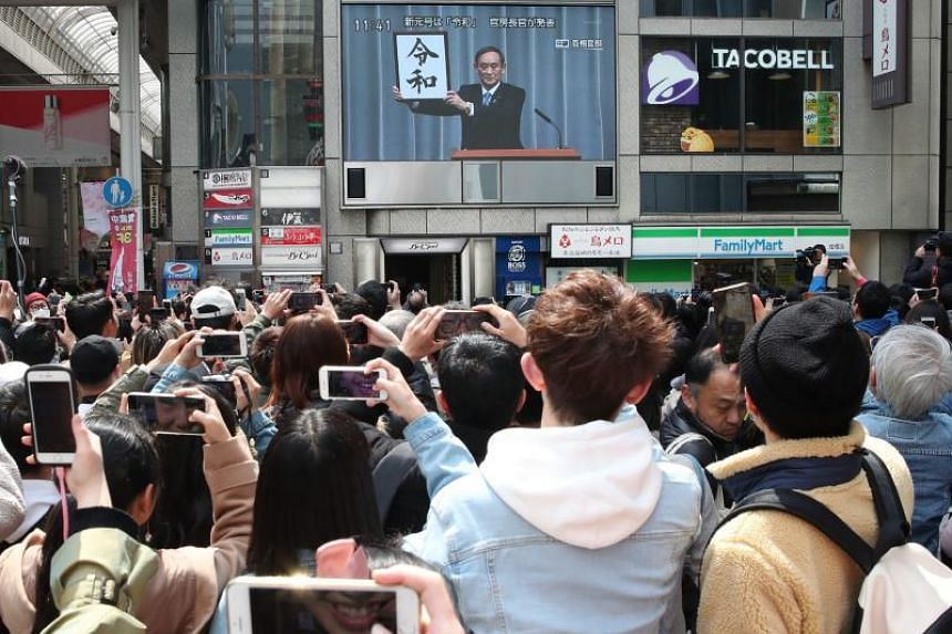 """People taking photos of a news programme reporting the announcement of the new era name """"Reiwa"""", in Tokyo on April 1, 2019."""