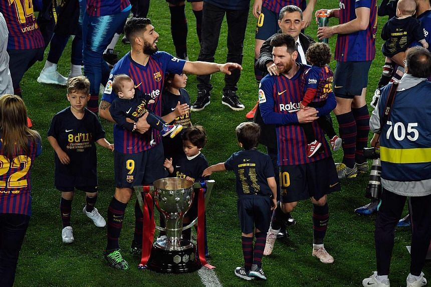 Barcelona's Luis Suarez and Lionel Messi, with their children, celebrating with the LaLiga trophy after beating Levante 1-0 at the Nou Camp on Saturday. It is Messi's eighth league title in 11 years, and the club's 26th overall.