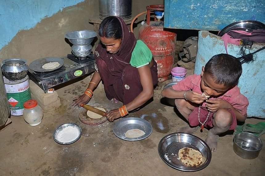 """Madam Reena Devi preparing food using a stove connected to a gas cylinder in Nisarpura village. She says her life changed when she got a cooking gas connection. But the """"free"""" kit came at a price."""