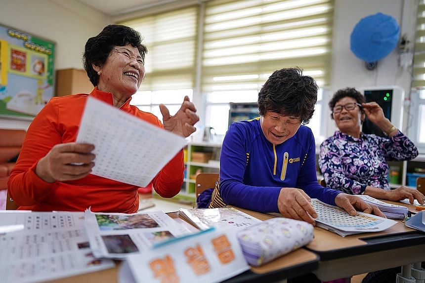From left: Madam Hwang Wol-geum, 70, Madam Kim Mae-ye, 64, and Madam Park Jong-sim, 75, learn to read in a first-grade class at Daegu Elementary, in Gangjin county, in south-western South Korea. Daegu Elementary has only 22 pupils in total, including