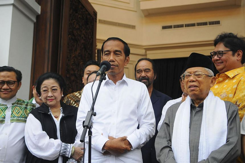 Indonesian President Joko Widodo (centre) and his running mate Ma'ruf Amin (right) at a press conference in Jakarta, on April 18, 2019.