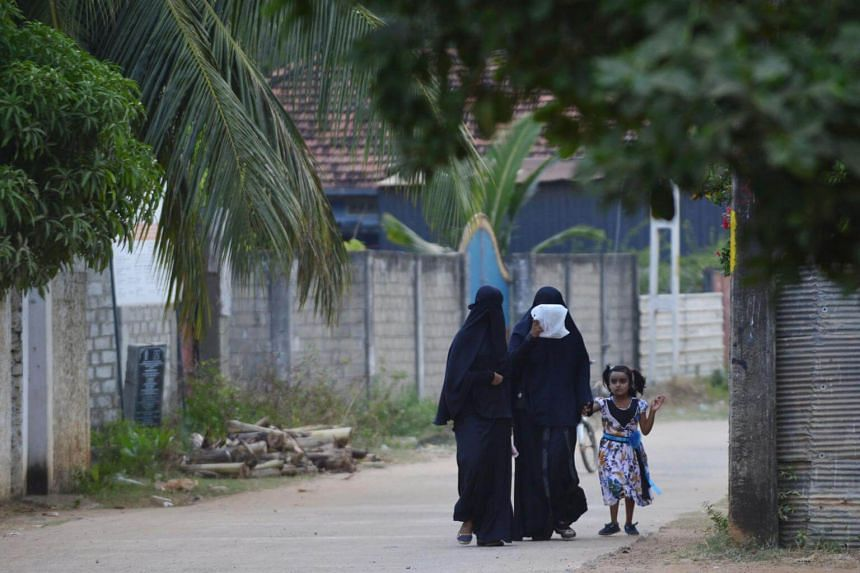 Sri Lankan Muslim women walk with a girl along a road in Kattankudy. Local Islamic clerics have urged Muslim women not to cover their faces amid fears of a backlash after the bombings.