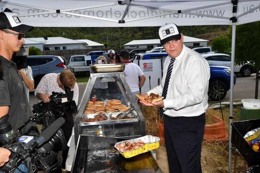 Australian Prime Minister Scott Morrison handing out bacon-and-egg rolls to workers at a construction site in Townsville last Friday during his election campaign. Putting the immigration policy back in the headlines is an attempt to remind voters of