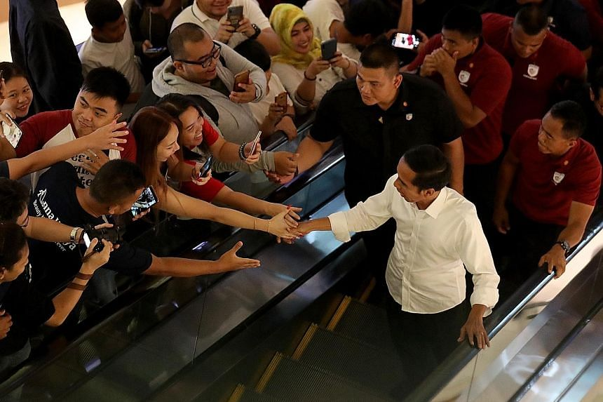 Based on 50 per cent of the ballots tallied by KPU, President Joko Widodo (in white) is 12.4 percentage points ahead of Mr Prabowo. PHOTO: EPA-EFE Presidential candidate Prabowo Subianto, a retired army general, at celebrations marking the 67th anniv