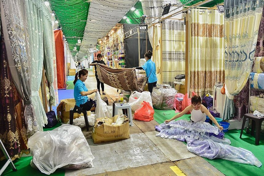 Workers from H. M. Curtain setting up their store yesterday at the Hari Raya Bazaar, which opens on Friday. The launch of the light-up will also see entertainers performing a medley of 1960s Malay songs.