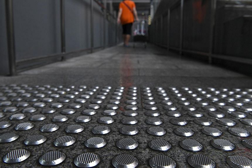 Nex shopping mall is replacing metal floor studs (left) around its premises after a man complained that a section of the studs becomes slippery in wet weather. They are meant to warn the visually impaired of upcoming stairs or escalators, and are sit