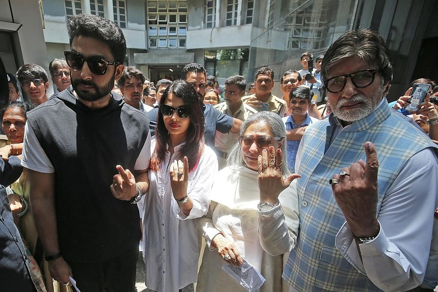 Bollywood star Amitabh Bachchan (right), his son Abhishek Bachchan, daughter-in-law Aishwarya Rai Bachchan and wife Jaya Bachchan, showing the ink marks on their fingers after casting their votes at a polling station in Mumbai, India, yesterday. PHOT