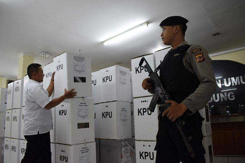 An Indonesian policeman stands guard as an official stacks boxes containing election results in Bandung, West Java, on April 29, 2019.