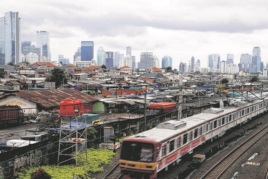 A commuter train is seen against the backdrop of high-rise buildings at Tanah Abang district in Jakarta, Indonesia.
