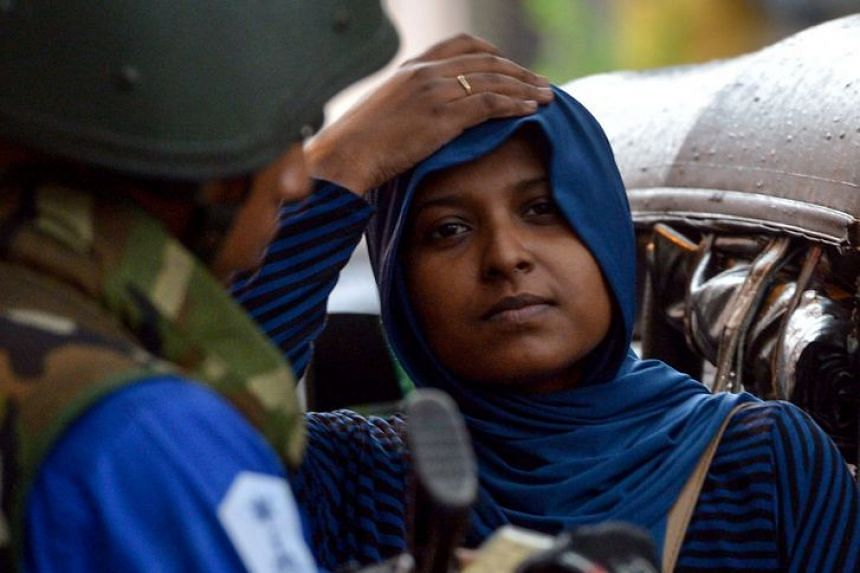 A Sri Lankan Muslim woman looks on at a checkpoint in Colombo.