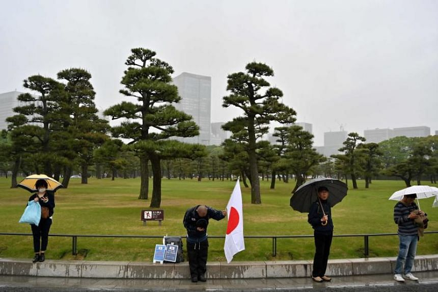 A man bows while holding a Japanese flag as people gather outside the Imperial Palace in Tokyo where the abdication ceremony for Japan's Emperor Akihito is taking place, on April 30, 2019.